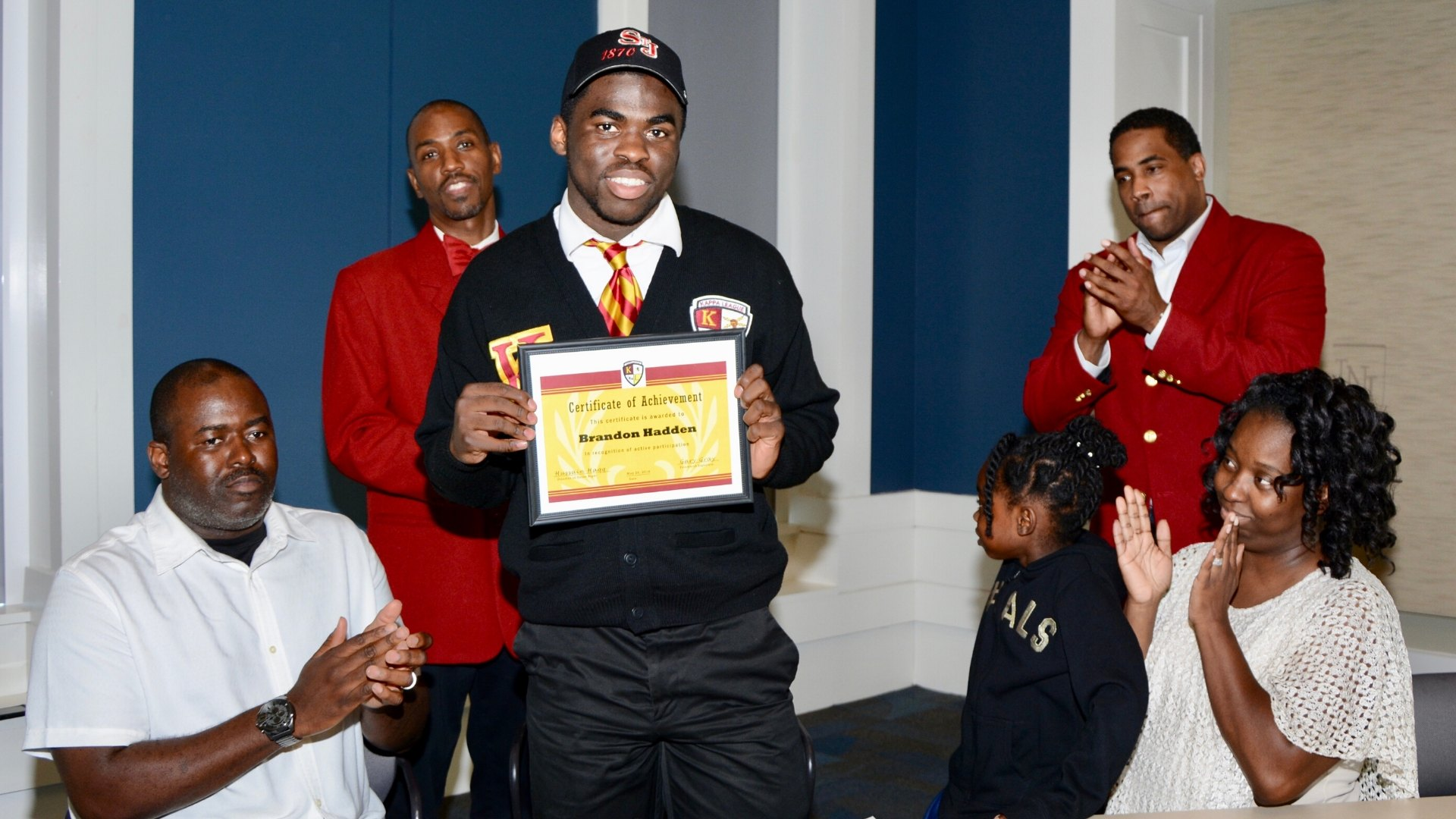 Photo of Young Man receiving an award at College signing Day event